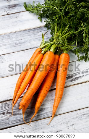 a fresh bunch of carrots on wood background - stock photo