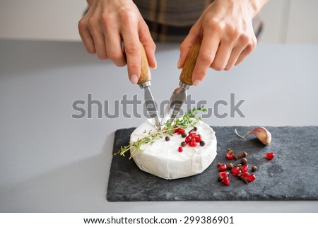 A fresh Camembert sits on a slate board. It is decorated with a sprig of fresh rosemary and a few pomegranate seeds. Here, a woman's hands are cutting into the cheese, preparing it to be served. - stock photo