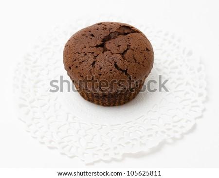 a fresh chocolate muffin (cake) on a lace napkin - stock photo