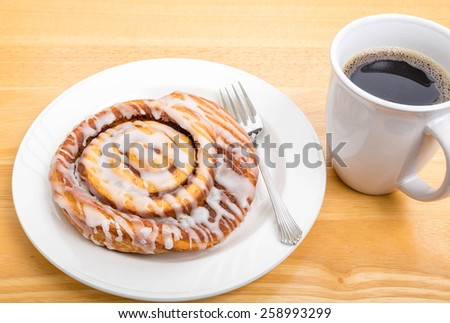 A fresh cinnamon roll on a plate with fork and a cup of coffee - stock photo