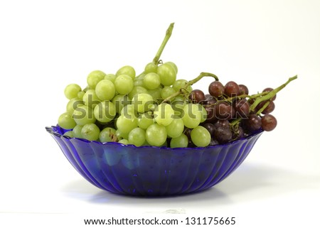 A fresh cluster of green and purple grapes isolated against a white background with room for copy - stock photo