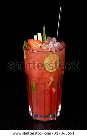 A fresh cocktail with watermelon, cucumbers, strawberries, and ice, on a black background.