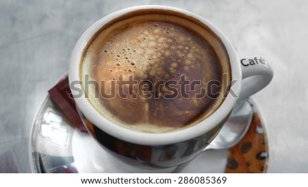 A fresh cup of coffee with saucer and teaspoon. - stock photo