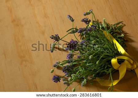 A fresh cut lavender bouquet on wooden surface lit by window light. - stock photo