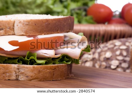 A fresh deli sandwich with tomatoes swiss chees, lettuce and lots of meat.