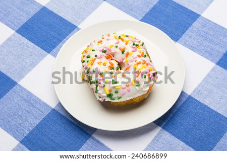 A fresh, delicious icing coated cake donut with sweet sprinkles on a classic, checkered diner tablecloth D - stock photo