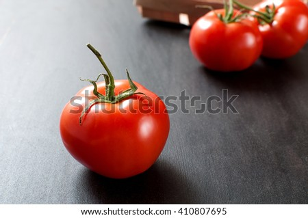 A fresh delicious red organic tomato and few tomatoes on a background lays on grey old kitchen table, horizontal image - stock photo