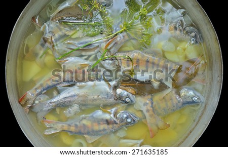 A fresh fish-soup in pot. Isolated on black. - stock photo