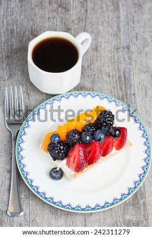 A fresh fruit tart served with a cup of coffee - stock photo