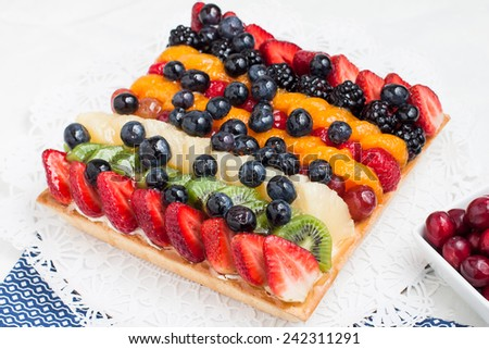 A fresh fruit tart viewed from above with bowl of fresh berries - stock photo
