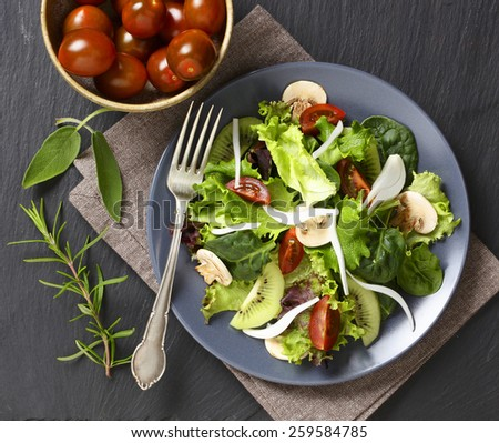 A fresh green salad with mushrooms and kiwi on a dark grey plate. - stock photo
