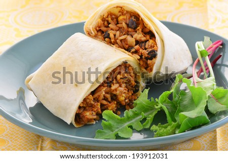 A fresh healthy lunch of chicken and black bean burrito with baby salad greens  - stock photo