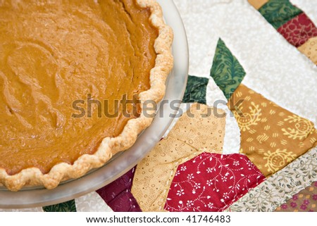 A fresh homemade pumpkin pie on a quilted table cloth.
