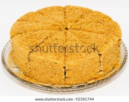 a fresh honey cake, cut, on a glass tray - stock photo