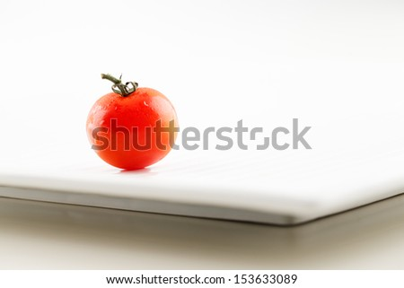 A fresh organic tomato with water droplets on a white ceramic plate