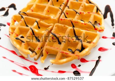 a fresh round waffle, served with chocolate and raspberry syrup - stock photo