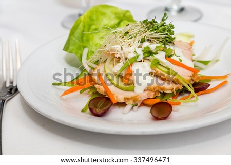 A fresh salad of butter lettuce, sprouts, sliced chicken, granny smith apples, carrots and grapes