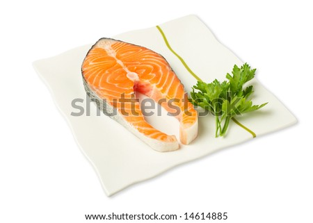 A fresh salmon steak on white dish with parsley