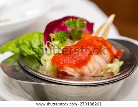 A fresh shrimp cocktail in silver bowl with red cocktail sauce - stock photo