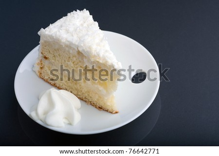A fresh slice of coconut cream cake on a white plate. - stock photo