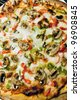 A fresh specialty pizza with extra toppings hot and fresh out of the oven. Shallow depth of field. - stock photo
