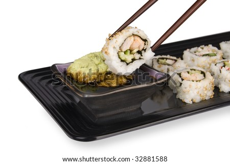 A fresh sushi roll of crab and fish being dipped into wasabi and soy sauce using chopsticks and an elegant serving tray. - stock photo