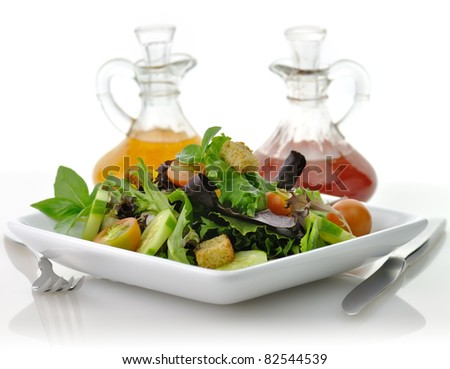 a fresh vegetable salad in a white dish with salad dressing - stock photo