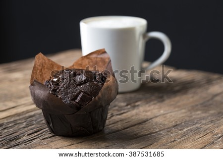 A freshly baked Chocolate Muffin and a Cappuccino coffee, sitting on an old rustic, wooden table. - stock photo
