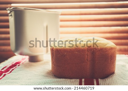 A freshly baked loaf of bread and a bread maker tin by the window bathed in sunlight