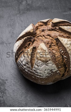 A Freshly baked organic bread on wooden table in Spain - stock photo