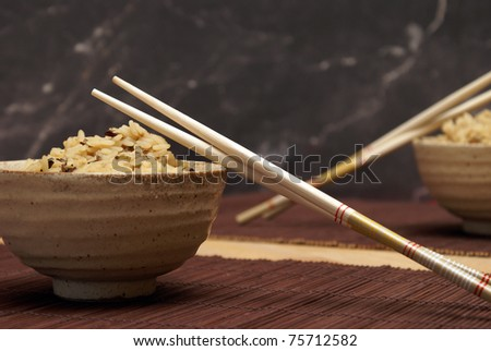 A freshly cooked bowl of rice with wooden chopsticks to enjoy a taste of the orient. - stock photo