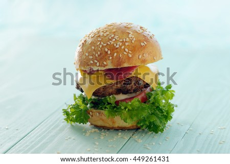 A freshly cooked hamburger on a light blue background.