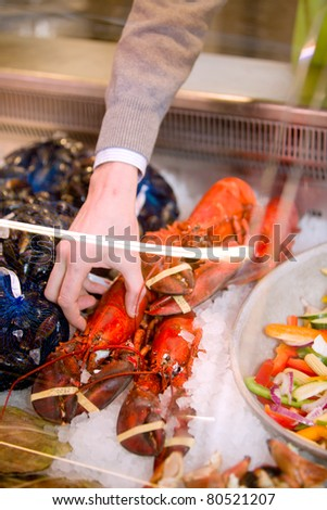 A freshly cooked lobster in a grocery store seafood display - stock photo