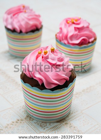 a freshly made creamy, pastel pink cupcake - stock photo