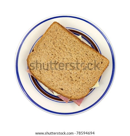 A freshly made turkey ham with white cheese on wheat bread sandwich on a blue striped plate. - stock photo