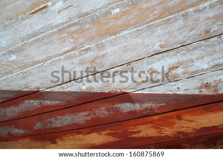 A freshly sanded and primed old lobster boat wooden hull in the paint shop of a boat builders workshop  - stock photo