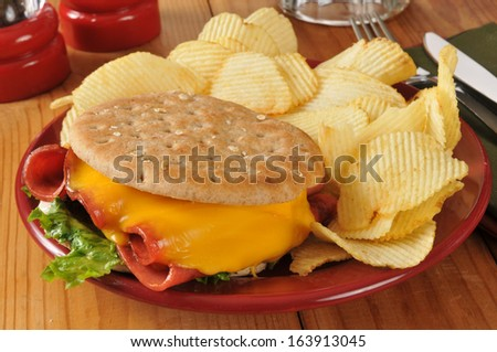 A fried bologna sandwich with potato chips - stock photo
