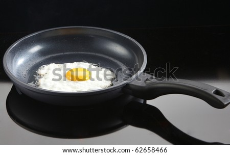 a fried chicken egg in a cast iron frying pan - stock photo