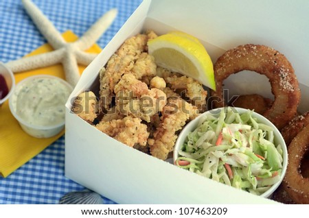 A fried clam strip dinner with onion rings and coleslaw.
