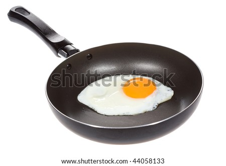 A fried egg in a frying pan on white background - stock photo