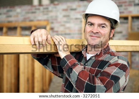 A friendly appealing construction worker in classic pose, carrying planks on the jobsite.  Model is actual construction worker. Authentic and accurate content depiction. - stock photo