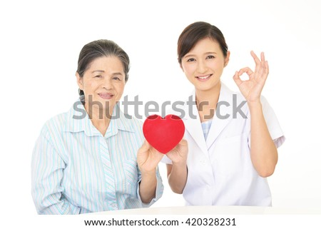 A friendly female doctor and an elderly woman - stock photo