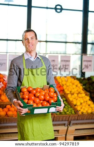 A friendly grocery store owner with a box of ripe tomatoes - stock photo
