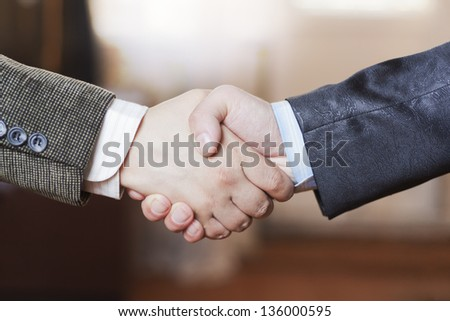 A friendly handshake two business partners in the office - stock photo