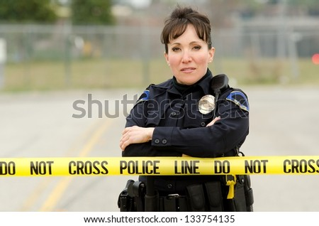A friendly looking female officer standing behind crime scene tape with her arms crossed. - stock photo
