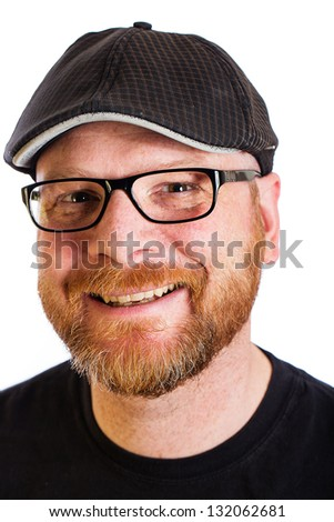A friendly man with a red beard wearing glasses and a duckbill hat.