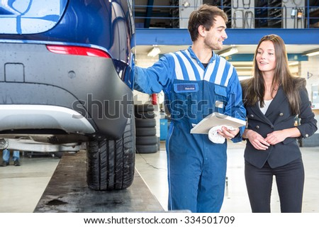 A friendly mechanic providing customer service to a young business woman, showing her the work he's done on her car, equipped with a new set of winter tires to ensure road safety. - stock photo