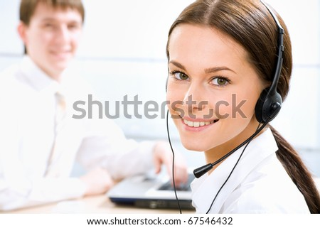 A friendly secretary/telephone operator in an office environment. - stock photo