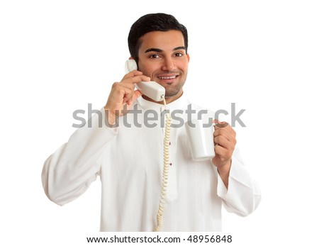A friendly smiling ethnic arab businessman on a telephone call.  He is holding a mug of coffee and is wearing traditional middle eastern or south east asian clothing. - stock photo