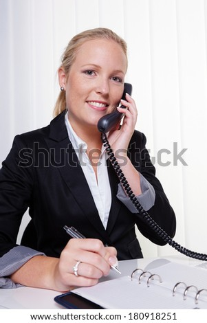 a friendly woman on the phone at her desk in the office and recorded dates on the calendar - stock photo